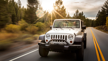 Photo of man driving jeep with female passenger on forest road