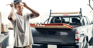 Contractor standing in front of pickup truck with plywood in the back
