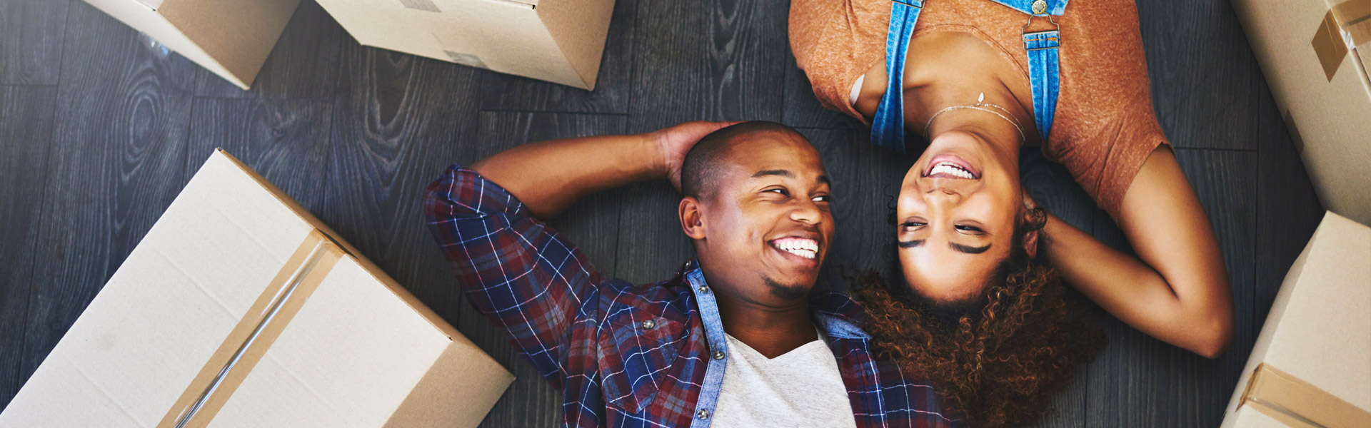 man and woman laying on floor smiling with packaged moving boxes around them