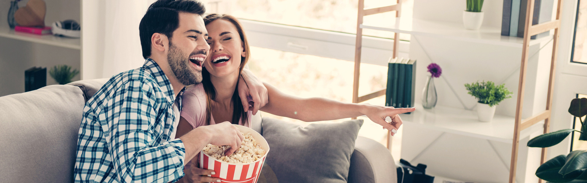 Couple at home eating popcorn laughing