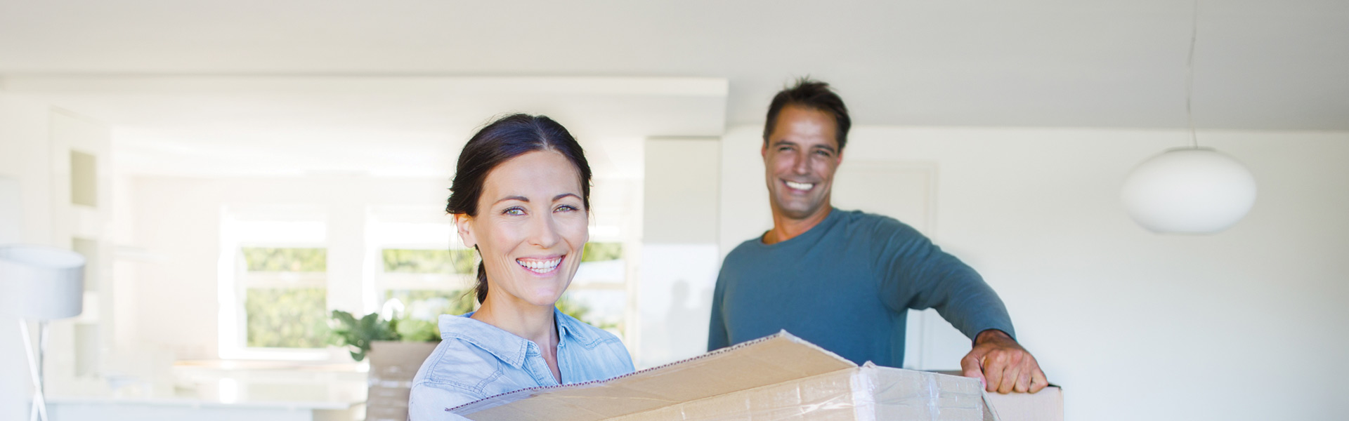 Man and woman moving boxes in new home smiling