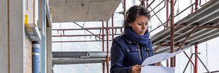 Woman reviewing blueprints on construction site