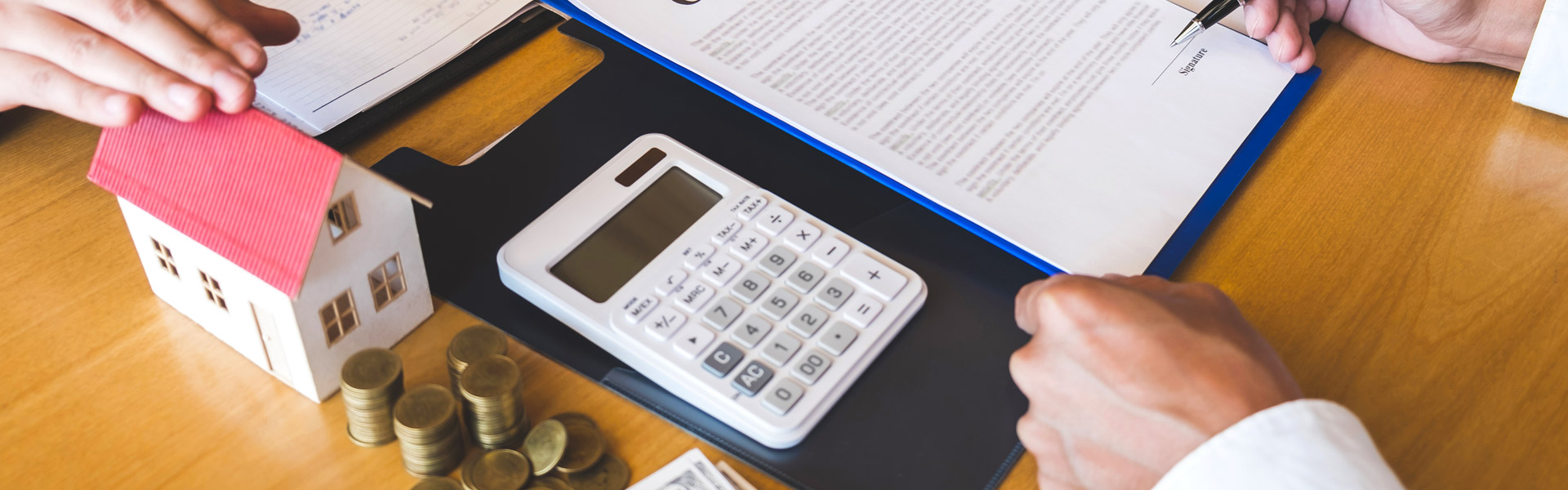 calculator, coins, and a small model home on a desk