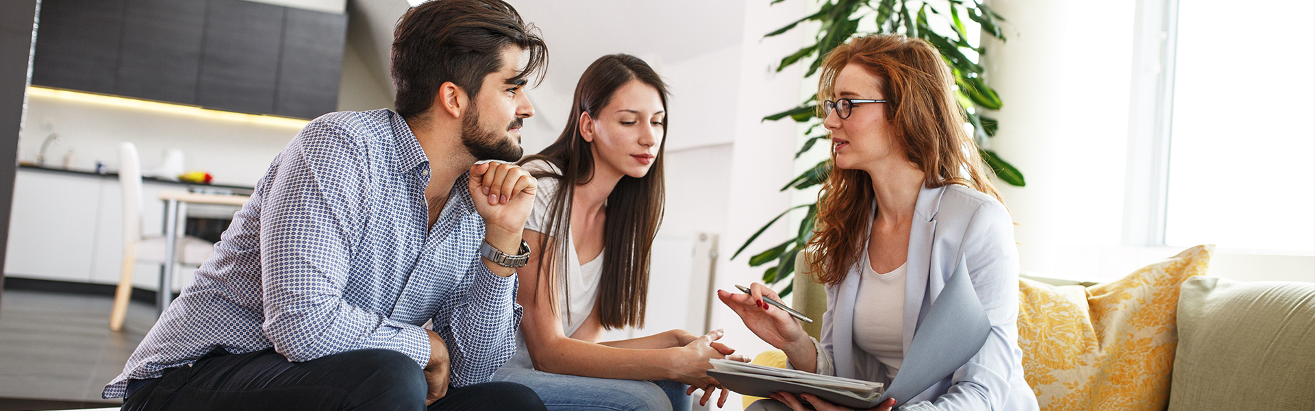 Young couple speaking with a female mortgage lender in a living room reviewing loan documents